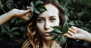 A-women-posing-with-green-leaves-on-face
