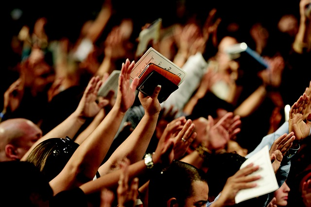 Picture-of-a-religious-conference-were-people-are-raising-their-hands